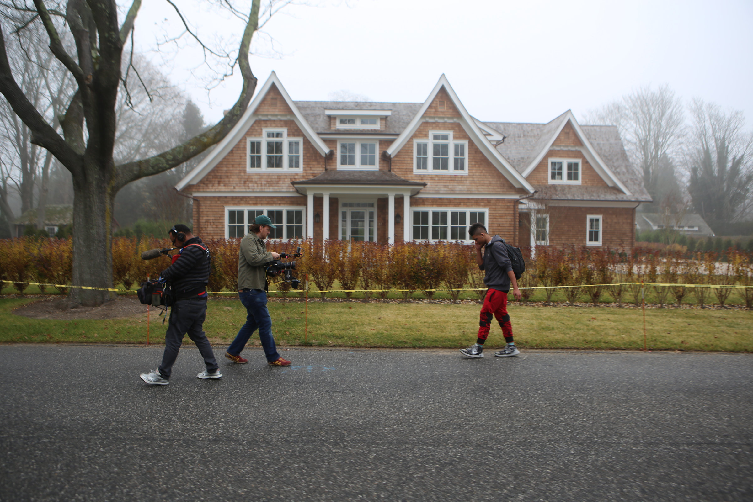 The documentary film crew follows JP Harding as he walks by a house in Bridgehampton.